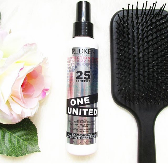 Redken One United Leave In Conditioner next to paddle brush and rose flower