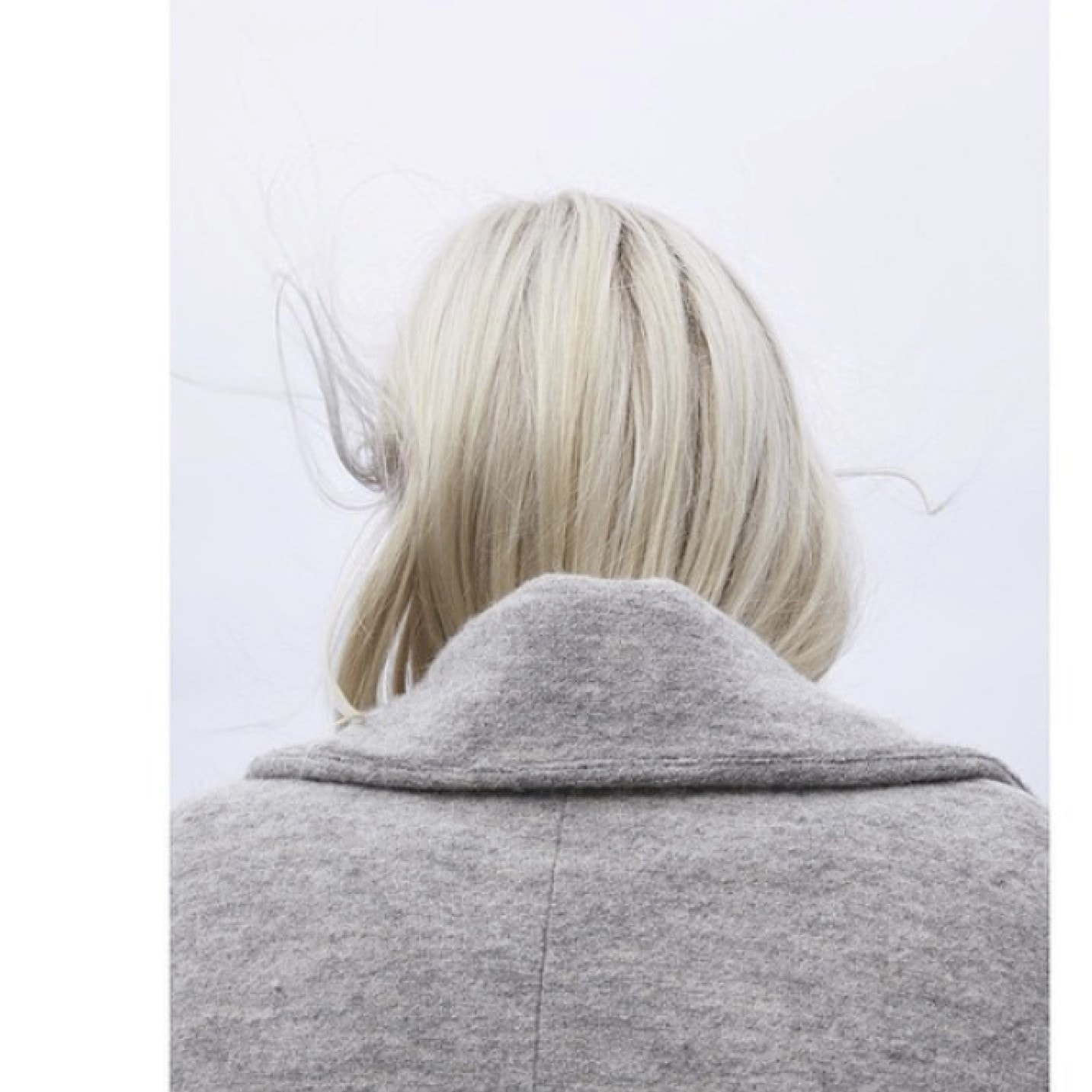 Platinum blonde hair tucked into gray coat